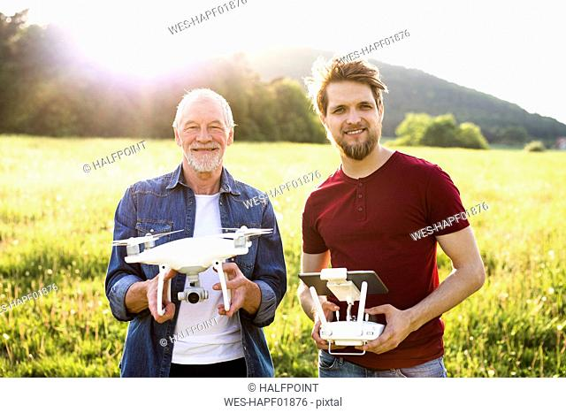 Portrait of senior father and his adult son with drone on a meadow