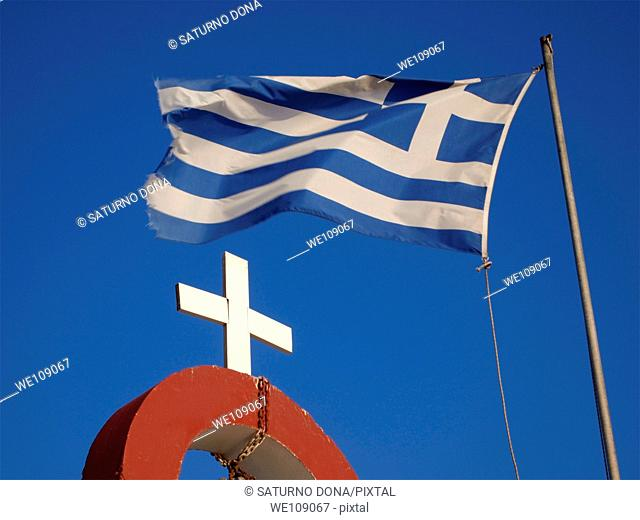 flying greek flag and cross of an orthodox church