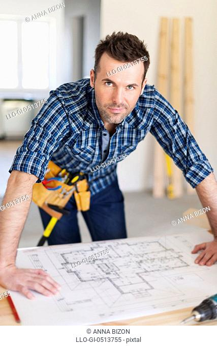 Portrait of handsome construction worker with home plans. Pilzno, Poland
