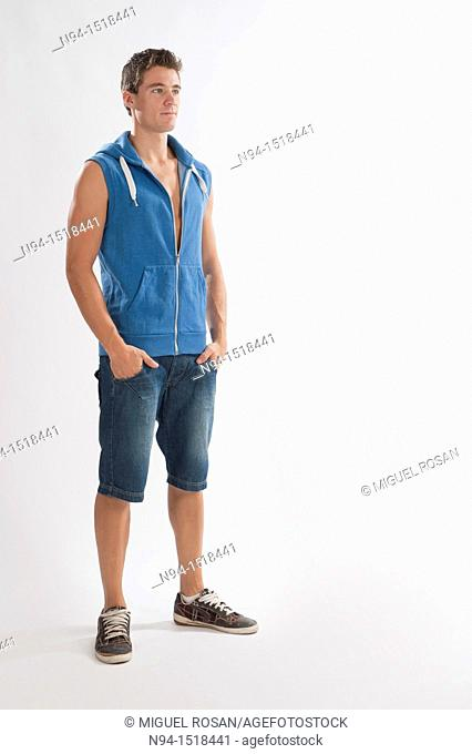 Full-body photograph of a teenage boy, with jeans and short blue sleeveless vest