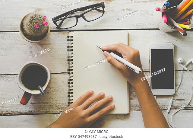 People are writing something in a white notebook with a cup of coffee and a telephone. On white wood floor