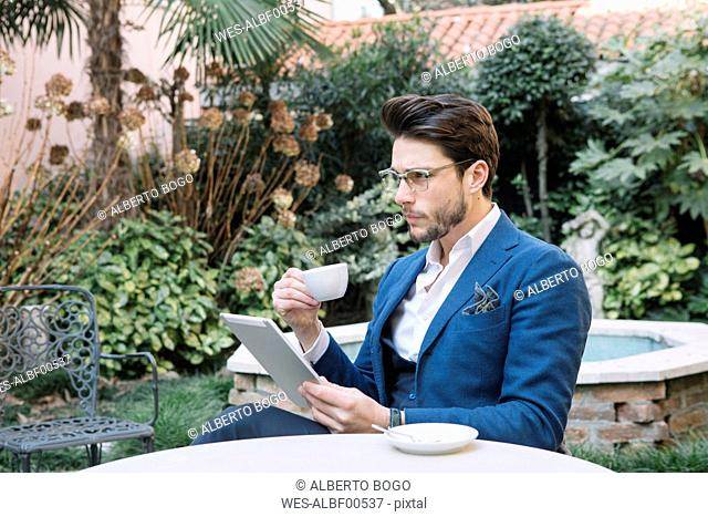 Elegant businessman using tablet in a garden cafe