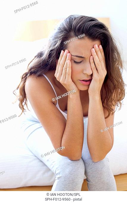 MODEL RELEASED. Woman sitting on bed touching her head and face in pain