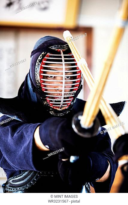 Close up of Japanese Kendo fighter wearing Kendo mask in combat pose