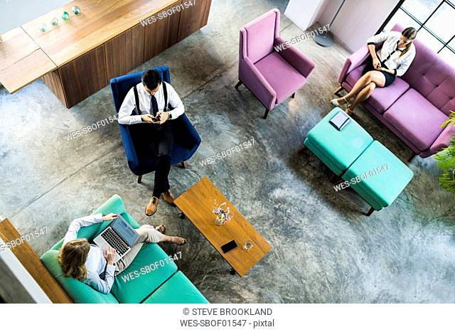 Top view of business colleagues working on laptop and smartphone in coworking space