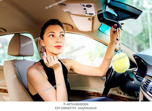 Beautiful woman paints her lips in the car