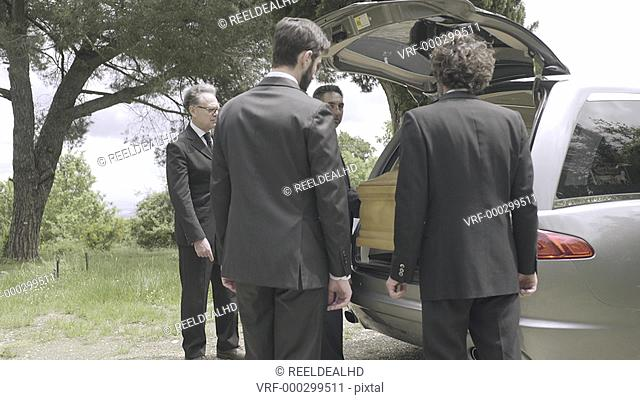 Pallbearers in hearse arriving with coffin at graveyard
