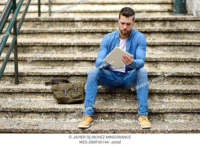 Young man sitting on stairs, working, using digital tablet
