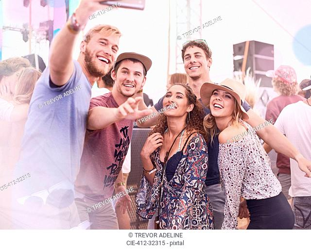 Young friends posing for selfie at music festival