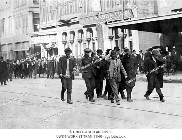 Indianapolis, Indiana: 1913 Hired strike breakers with their hats pulled over their faces being driven from a streetcar and back to the company barns