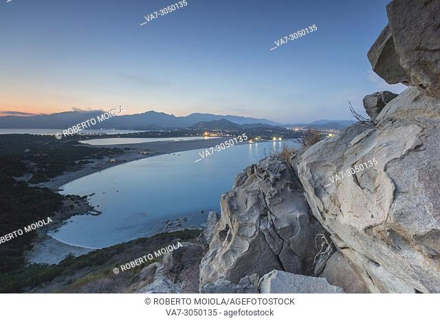 Top view of the bay with sandy beaches and lights of a village at dusk Porto Giunco Villasimius Cagliari Sardinia Italy Europe