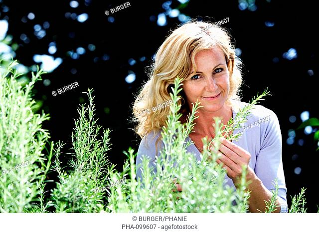 Woman picking rosemary from the garden