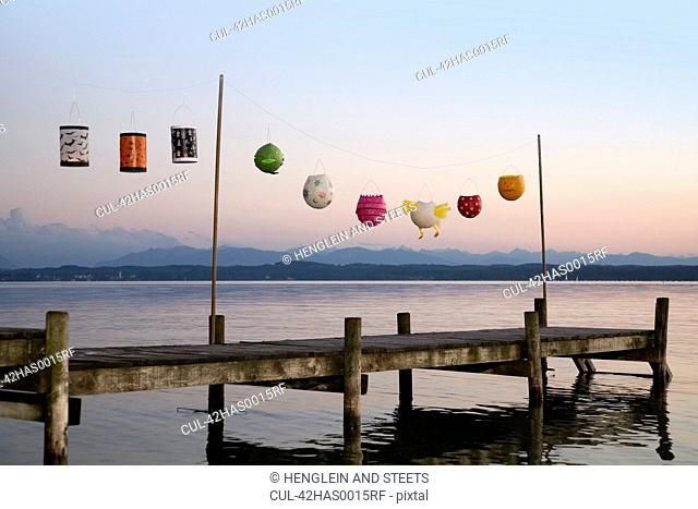 Paper lanterns strung up on wooden pier