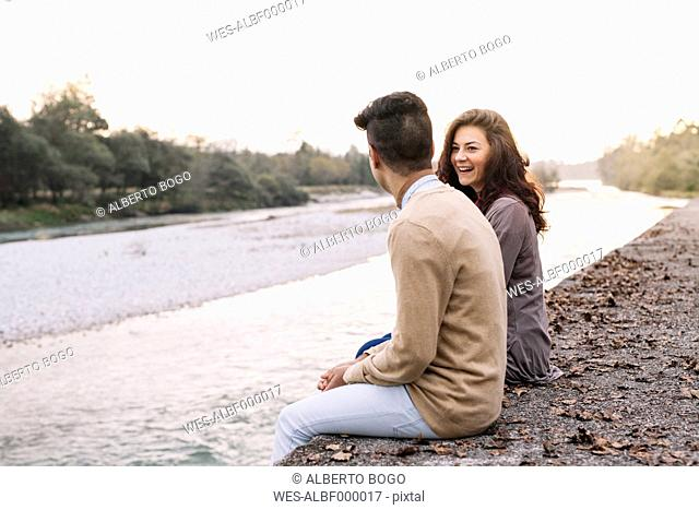 Italy, Belluno, young couple sitting in front of a river