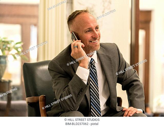 Caucasian businessman sitting in armchair talking on cell phone