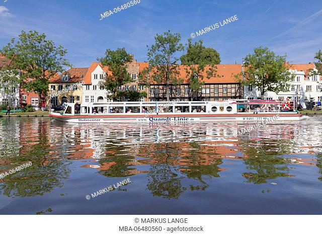 Excursion boat on the Stadttrave (river) with view at the Old Town of Lübeck, Schleswig Holstein, Germany