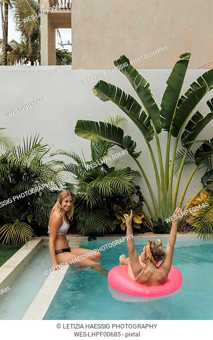 Two happy young women relaxing in swimming pool