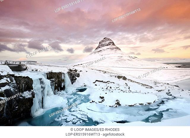 Winter sunrise over Kirkjufellsfoss waterfalls backed by Kirkjufell or Church mountain