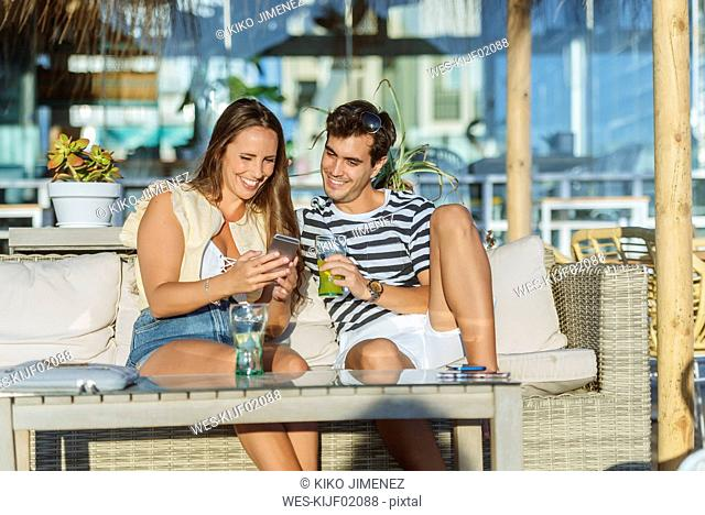Happy young couple sitting on the terrace of a bar looking at cell phone