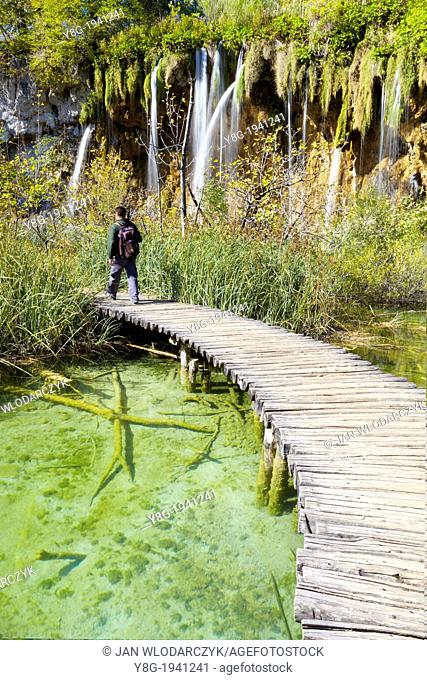 Croatia - Plitvice Lakes National Park, water cascade between lakes and wooden footbridge for tourists, central Croatia
