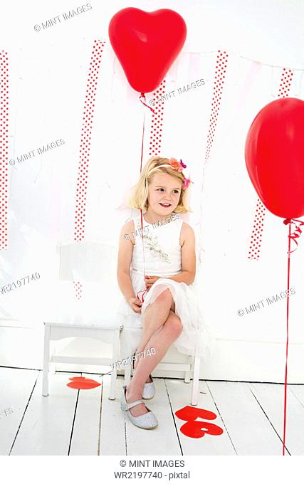 Young girl posing for a picture in a photographers studio, surrounded by red balloons