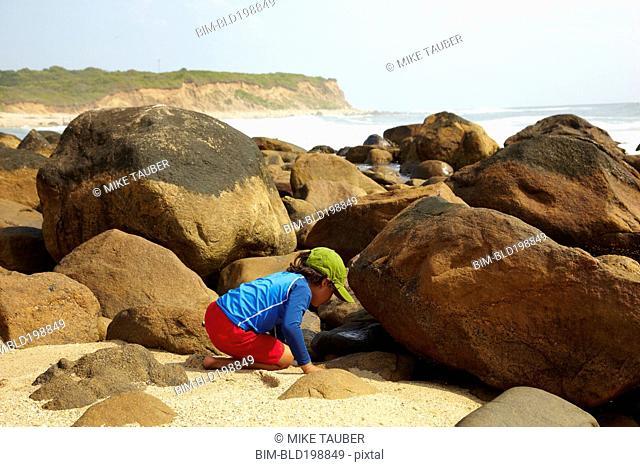 Mixed race boy looking underneath rocks