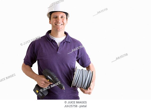 Electrician in hard-hat holding spool of wire and drill