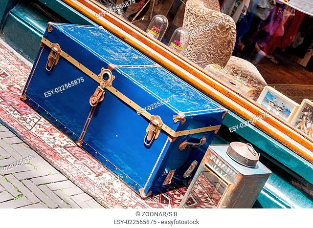 Large, old, blue travel chest at the window of a s
