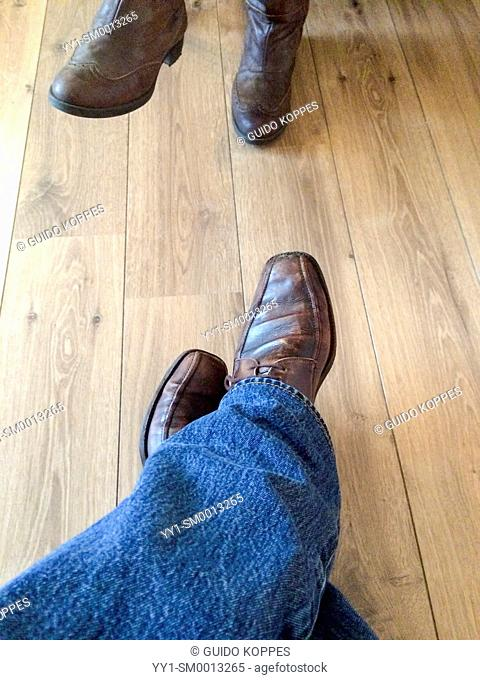 Breda, Netherlands. Two pair of feet, opposite to each other, during a conversation