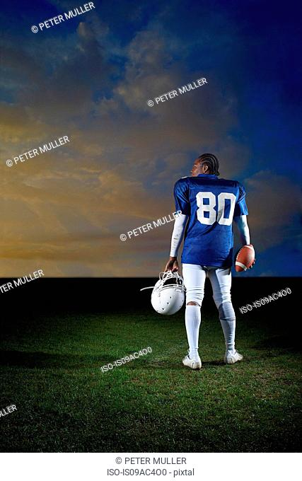 Rear view of American football player holding helmet