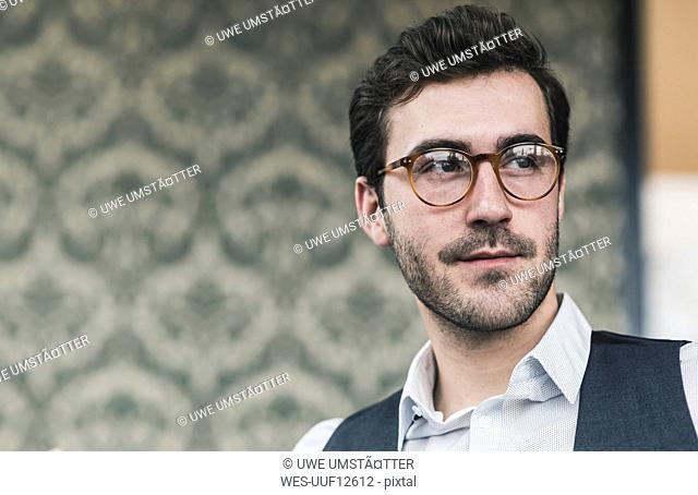 Portrait of young man wearing glasses looking sideways