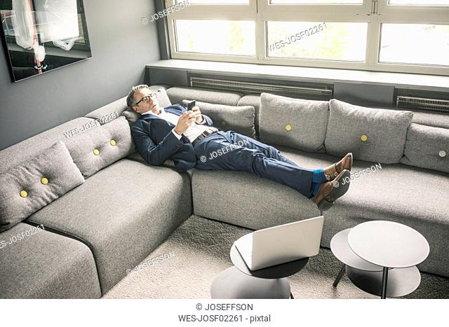 Mature businessman lying on couch using cell phone