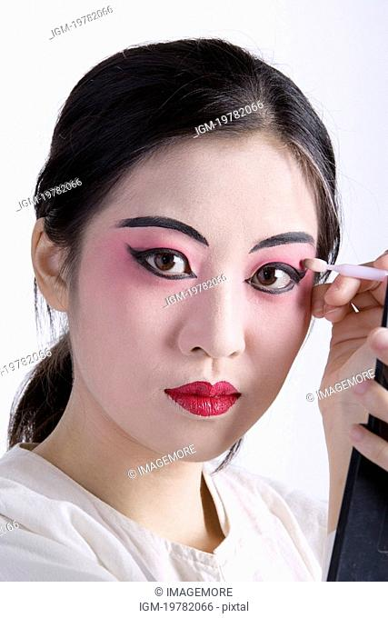 Beijing Opera performer preparing make-up