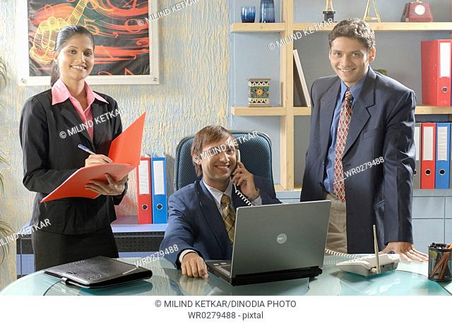 South Asian Indian businessmen and woman talking on phone standing in his office MR 670D , 670F ,670G