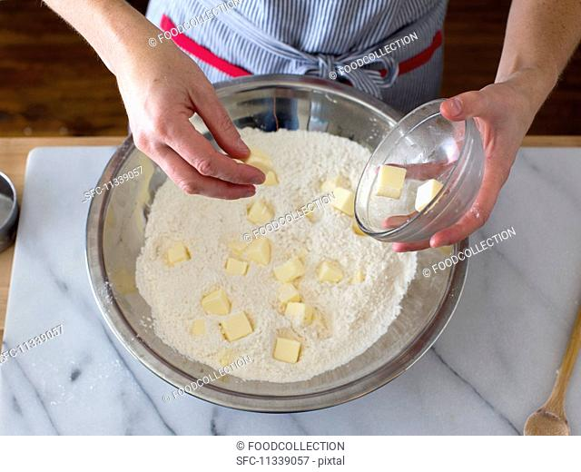 Diced butter being added to flour in a stainless steel bowl