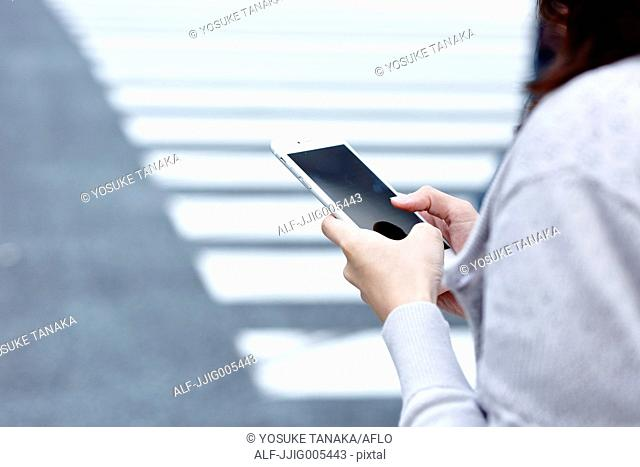 Fashionable Japanese woman with smartphone in luxury Tokyo area, Tokyo, Japan