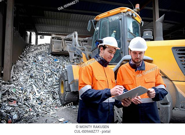 Workers checking clip chart in scrap metal yard
