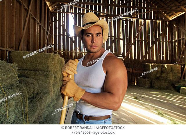 Rancher cleaning the barn. Poway, California. USA