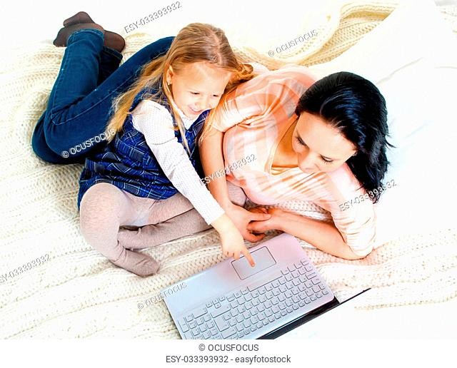 happy blonde haired daughter with her mum with brunette hair sitting on a bed sofa working on computer