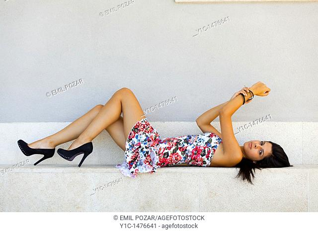 Attractive young woman in a colorful flowery dress is lying down on a step