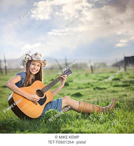 Cowgirl sitting in field playing guitar