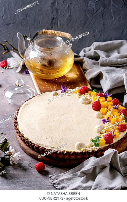 Homemade chocolate tart decorated by mango, raspberries, mint, puffed rice and edible flowers served with glass teapot and textile linen over gray texture table