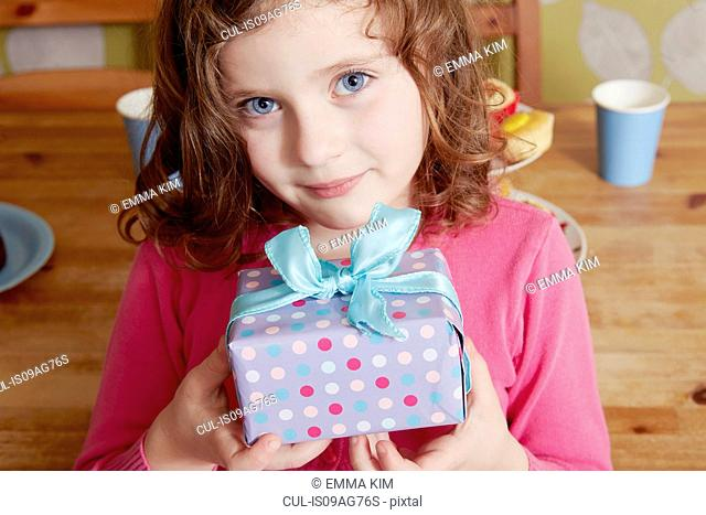 Portrait of girl holding birthday present