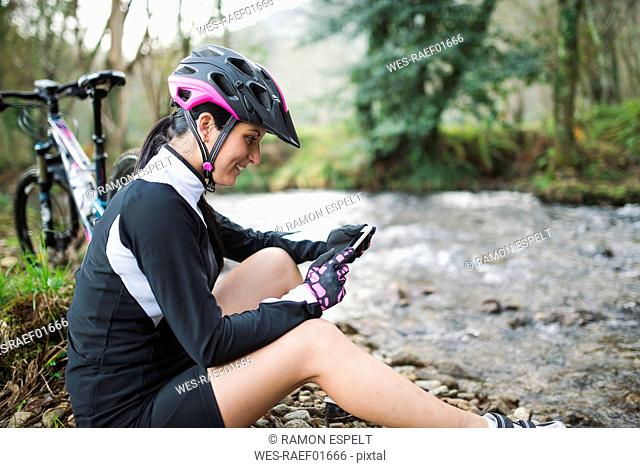 Smiling woman with mountain bike resting in nature checking her cell phone