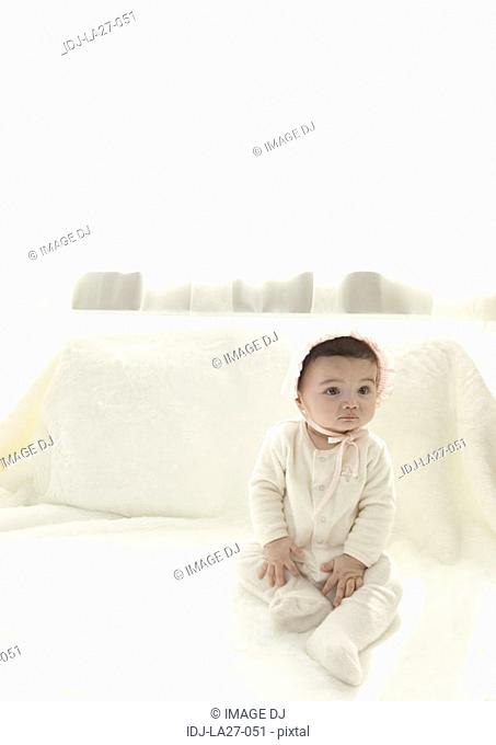 High angle view of a baby girl sitting on a bed