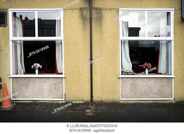Close up of two windows with vases of flowers in each one in a building. Saltaire, Shipley, Yorkshire, England,  United Kingdom., Europe