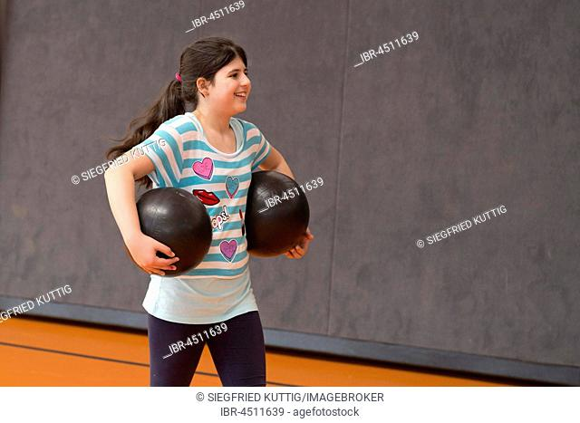 Schoolgirl playing ball in the gym, physical education, primary school, Lower Saxony, Germany