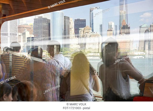 Reflection of people on Staten Island Ferry looking at buildings, New York City, New York, USA