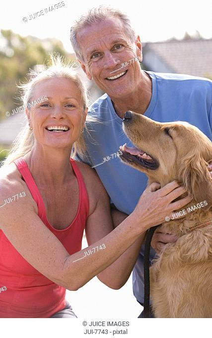 Active senior couple, in sportswear, stroking golden retriever, smiling, portrait