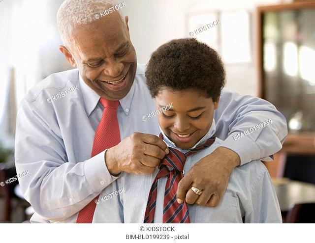 Black grandfather tying grandson's necktie